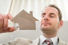 Hombre de negocios con rompecabezas de la forma de la casa Foto de archivo