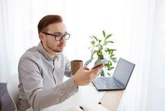 Hombre de negocios con smarphone y café en la oficina Imagen de archivo