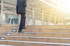 Hombre de negocios con smartphone que camina encima de las escaleras a la oficina Imagen de archivo libre de regalías