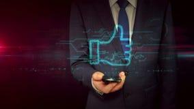 Hombre de negocios con smartphone y pulgar como concepto del holograma del símbolo almacen de video