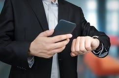 Hombre de negocios con smartphone y smartwatch en oficina Fotos de archivo libres de regalías
