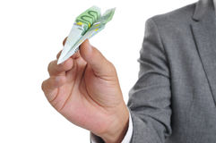 Hombre de negocios con un avión de papel hecho con un billete de banco del euro 100 Imagen de archivo libre de regalías