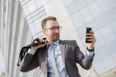 Hombre de negocios con un bolso sobre su hombro usando el teléfono elegante en el franco Imagenes de archivo