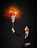Hombre de negocios con un bulbo de la explosión Imagen de archivo libre de regalías