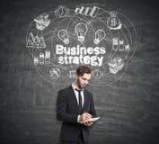 Hombre de negocios con un cuaderno que se coloca cerca de una pizarra con la estrategia empresarial que dibuja en ella Fotos de archivo
