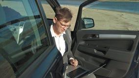 Hombre de negocios con un funcionamiento de la maleta del ordenador portátil que se relaja en la playa cerca de su coche almacen de metraje de vídeo