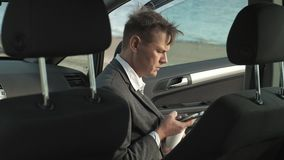 Hombre de negocios con un funcionamiento de la maleta del ordenador portátil que se relaja en la playa cerca de su coche metrajes