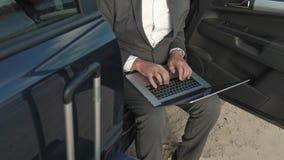 Hombre de negocios con un funcionamiento de la maleta del ordenador portátil que se relaja en la playa cerca de su coche almacen de video