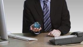 Hombre de negocios con un globo rotatorio en su mano almacen de video