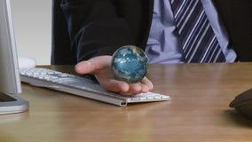 Hombre de negocios con un globo rotatorio en su mano abierta almacen de metraje de vídeo