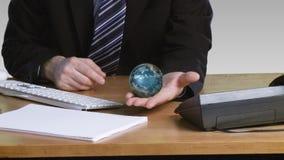 Hombre de negocios con un globo terrestre rotatorio en su mano abierta almacen de video