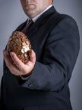Hombre de negocios con un huevo eurocent Imagen de archivo libre de regalías