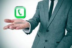 Hombre de negocios con un icono del teléfono en su mano Fotos de archivo libres de regalías