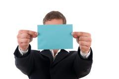Hombre de negocios con un infront azul de la carta su cara Foto de archivo libre de regalías