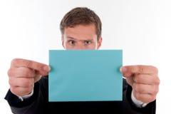 Hombre de negocios con un infront azul de la carta su cara Fotografía de archivo libre de regalías