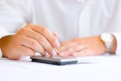 Hombre de negocios con un móvil de la pantalla táctil Imagen de archivo libre de regalías
