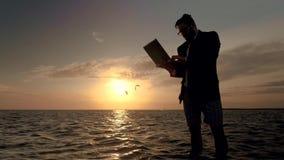 Hombre de negocios con un ordenador portátil en el medio del mar en el fondo de una puesta del sol magnífica almacen de video