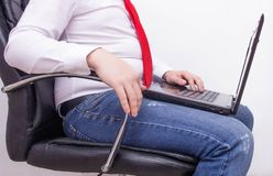 Hombre de negocios con un ordenador portátil que se sienta en una silla de la oficina con un estómago retractable grueso, flatule foto de archivo