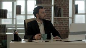 Hombre de negocios con un ordenador portátil y un té que miran su reloj imagen de archivo libre de regalías
