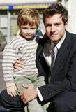 Hombre de negocios con un pequeño muchacho Imagen de archivo libre de regalías