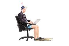 Hombre de negocios con un tubo respirador que trabaja en el ordenador portátil Imagen de archivo