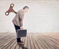 Hombre de negocios con un viento encima de la llave imagen de archivo
