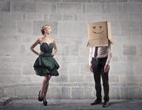 Hombre de negocios con una caja en su cabeza y una mujer hermosa Imagen de archivo libre de regalías