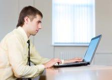 Hombre de negocios concentrado con la computadora portátil Imagen de archivo libre de regalías