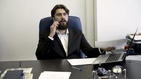 Hombre de negocios concentrado, nervioso, joven, barbudo en el teléfono, sentándose en butaca de cuero azul en la oficina enojado