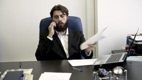 Hombre de negocios concentrado, nervioso, joven, barbudo en el teléfono, sentándose en butaca de cuero azul en la oficina enojado almacen de video