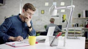 Hombre de negocios concentrado productivo que inclina el trabajo de oficina detrás de acabado en el ordenador portátil, encargado almacen de metraje de vídeo