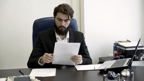 Hombre de negocios concentrado, serio, joven, barbudo que se sienta en butaca de cuero azul en la oficina y que lee los papeles almacen de metraje de vídeo