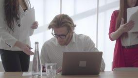 Hombre de negocios confiado acertado del retrato en los vidrios que se sientan en una oficina cómoda ligera con netbook en la tab almacen de metraje de vídeo