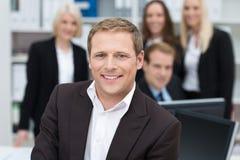 Hombre de negocios confiado apoyado por su equipo Imagen de archivo libre de regalías