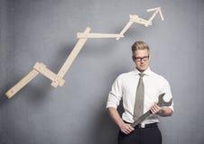 Hombre de negocios confiado con la llave y el gráfico. Imágenes de archivo libres de regalías
