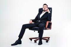 Hombre de negocios confiado confiado con la barba que se sienta en silla de la oficina imágenes de archivo libres de regalías