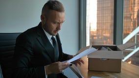 Hombre de negocios confiado en traje formal con la caja móvil en la oficina que desempaqueta artículos almacen de video