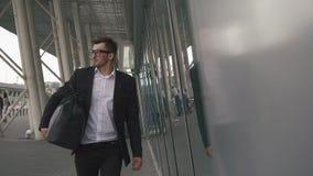 Hombre de negocios confiado joven con la maleta en terminal de aeropuerto moderno Concepto del individuo del inconformista que vi metrajes