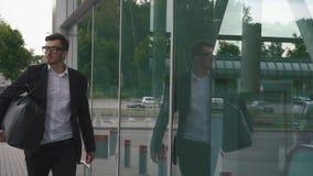 Hombre de negocios confiado joven con la maleta en terminal de aeropuerto moderno en el fondo de la pared de cristal Inconformist almacen de metraje de vídeo