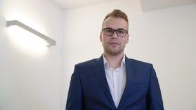 Hombre de negocios confiado joven en vidrios que comprueba el tiempo metrajes