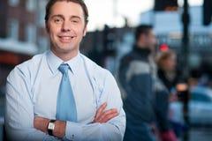 Hombre de negocios confiado que presenta, fondo de la calle imagenes de archivo