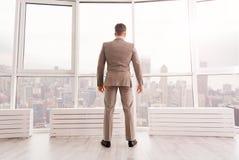 Hombre de negocios confiado que se coloca en su oficina Fotos de archivo libres de regalías