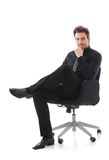 Hombre de negocios confiado que se sienta en la sonrisa de la silla Imagen de archivo libre de regalías