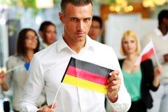 Hombre de negocios confiado que sostiene la bandera de Alemania Foto de archivo