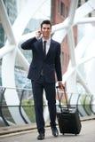 Hombre de negocios confiado que viaja con el teléfono y el bolso Foto de archivo libre de regalías