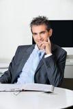 Hombre de negocios confiado Sitting At Desk imagen de archivo libre de regalías