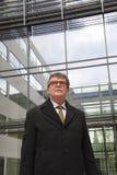 Hombre de negocios confiado y resuelto en el traje que se coloca delante del edificio de cristal moderno Fotografía de archivo libre de regalías