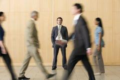 Hombre de negocios confidente con las personas que recorren más allá de él Fotos de archivo libres de regalías