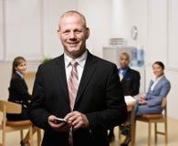 Hombre de negocios confidente con los compañeros de trabajo Fotos de archivo libres de regalías