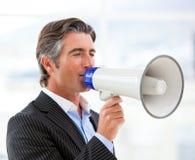 Hombre de negocios confidente que grita a través de un megáfono Imagenes de archivo
